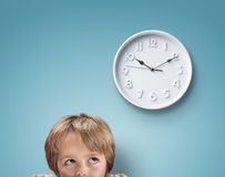 Boy looking up at a clock Stock Images