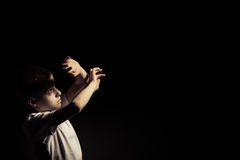 Boy Looking Up While Covering Light Against Black Royalty Free Stock Photos