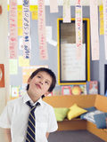 Boy Looking Up At Paper Strips In Class Stock Photos