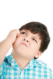 Boy looking up and scratches his head Royalty Free Stock Photo