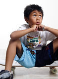 Boy looking up while sitting on his skateboard stock images