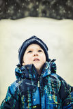 Boy Looking Up at Snow Falling - Retro stock images