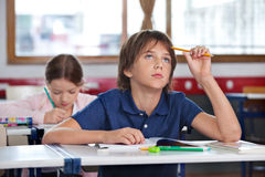 Boy Looking Up While Studying In Classroom. Thoughtful boy looking up while studying with classmate in background at classroom Stock Image