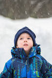 Boy Looking Up in Wonder at Snow Falling. An cute young boy is outside looking up in wonder at the snow falling during the winter season.  Room for copy space Royalty Free Stock Photo