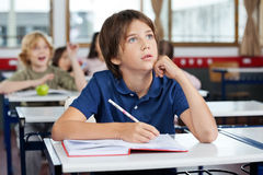 Boy Looking Up While Writing At Desk. Little boy looking up while writing at desk with friends in background Stock Photos