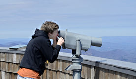 Boy Looking at View. A young boy on Brasstown Bald looking at the view with a telescope royalty free stock photo
