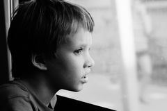 Boy looking through the window Stock Image