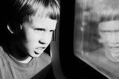 Boy looking through the window Royalty Free Stock Photos