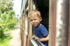 Boy is looking through the window. Cute boy is looking through the window in the Sri Lanka train with a skepticism on his face royalty free stock photo