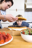 Boy Looking At woman Preparing Cake Stock Photography