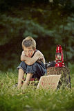 Boy looking for work. Young unemployed boy sitting near stump with sign looking for work Stock Image