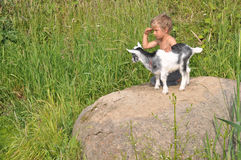 A boy looks afar, playing the young goat Royalty Free Stock Photo