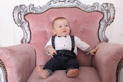 Family New Year`s concept. Child boy sits in a chair. The boy looks away. Child boy sits in a pink chair stock image