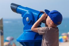 Boy looks at away on sea in monocular on sea beach stock photo