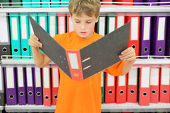 Boy looks big folder and stands near to shelves Stock Photo