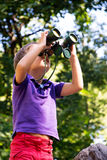 Boy looks through binoculars in forest Stock Photography