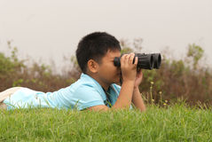 Boy looks into binoculars lying on top of hill . Stock Photography
