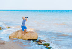 Boy looks through binoculars. At sea royalty free stock photos