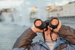 Boy looks through binoculars at  sunset Stock Images