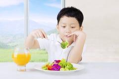 Boy looks dislike vegetables Royalty Free Stock Photography