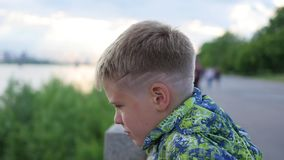 The boy looks into the distance on the waterfront. panoramic view stock video