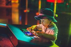 The boy looks an electronic map of the sky on the screen.  stock photos