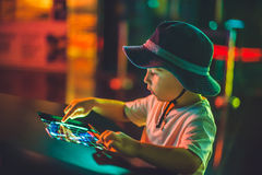 The boy looks an electronic map of the sky on the screen.  stock image