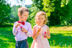 Boy looks at the girl makes soap bubbles Stock Images