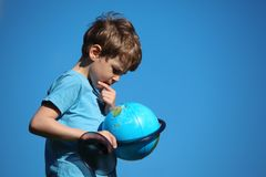 Boy looks on globe against sky Stock Photo