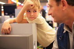 Boy looks on grandfather in shop Stock Photography