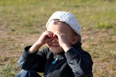 A boy looks through hands like binocular Royalty Free Stock Image