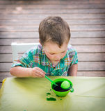 Boy Looks at His Easter Egg in the Green Dye Stock Photos