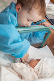 Boy feeding a newborn sister Stock Photography