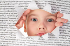 Boy looks into the hole in the sheet Royalty Free Stock Images