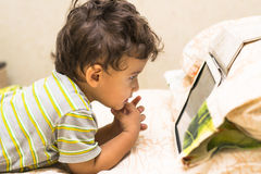 Boy looks at the iPad. The boy looks at the iPad on the bed Royalty Free Stock Image