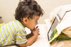 Boy looks at the iPad Royalty Free Stock Image