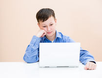 The boy looks at the laptop. At the table Stock Photos