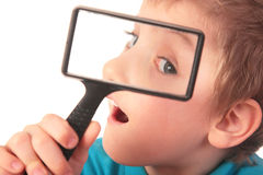 Boy looks through  magnifier Stock Image