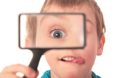 Boy looks through  magnifier Royalty Free Stock Image
