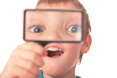Boy looks through  magnifier with surprise Royalty Free Stock Photo