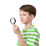The boy looks through a magnifying glass Royalty Free Stock Images