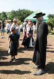 A boy looks at a man in plague doctor costume at Renaissance Festival Stock Image