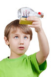 Boy looks at model of tallship in bottle Royalty Free Stock Photography