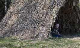 The boy looks out of the straw tent. Straw tent on the green grass in the parkюThe boy looks out of the straw tent Royalty Free Stock Image