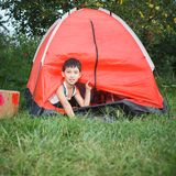 Boy looks out from a tent Royalty Free Stock Photography