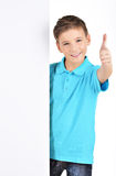 Boy looks out from the  white banner with thumbs up gesture Stock Images