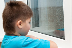Boy looks out the window Stock Photos