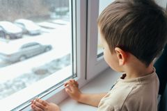 The boy looks out the window. A boy looks out the window, the concept of loneliness, expectations, an orphan boy, an orphanage, an orphanage Royalty Free Stock Image