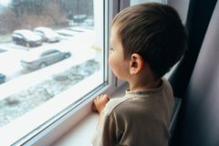 The boy looks out the window. A boy looks out the window, the concept of loneliness, expectations, an orphan boy, an orphanage, an orphanage Stock Image