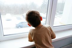The boy looks out the window. A boy looks out the window, the concept of loneliness, expectations, an orphan boy, an orphanage, an orphanage Stock Photo
